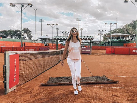 Ariana on clay tennis court wearing stylish white tennis outfit