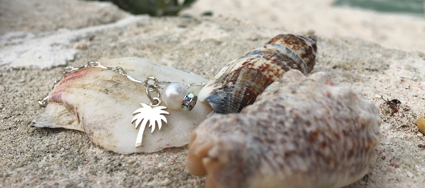 Sea inspired bracelet with one pearl and one sea inspired charm of a palm tree
