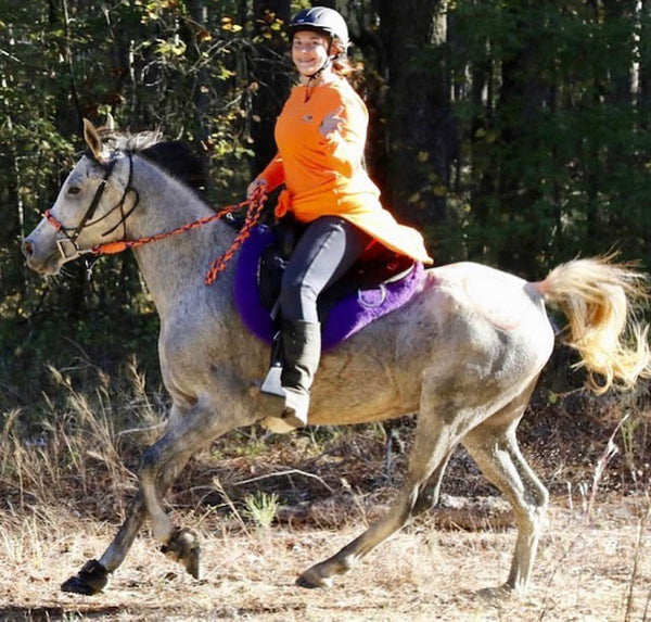 A woman riding a grey horse wearing Scoot Boots in a horse riding competition