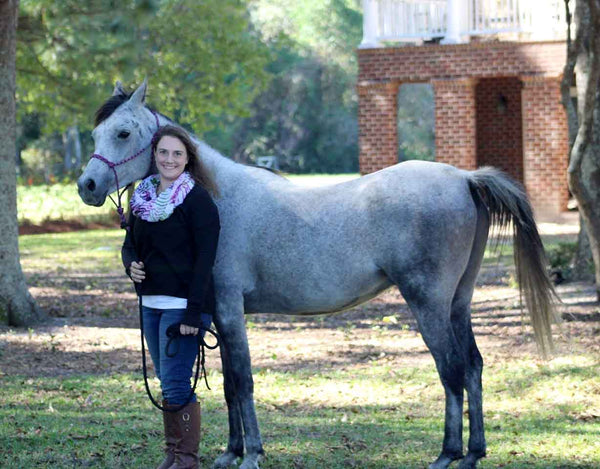 Woman posing with her grey horse on the grass