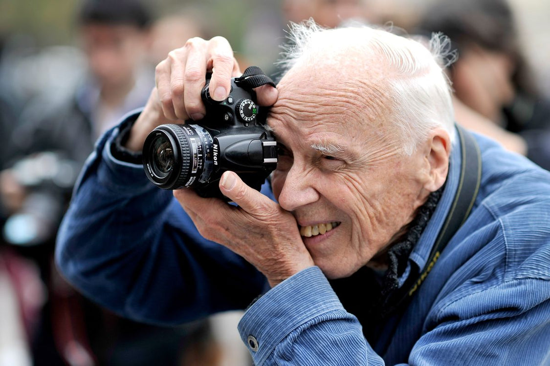 Bill Cunningham, a street fashion photographer in his iconic blue jacket is snapping a shot.