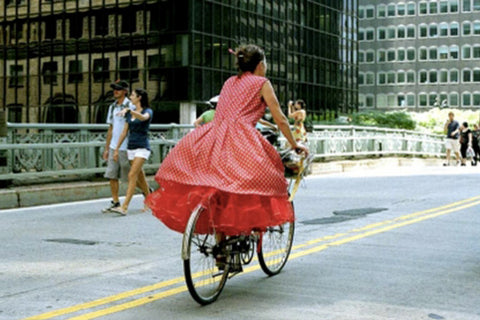 A photo of a woman in a puffy layered red dress on a bike taken by Bill Cunningham in NY.