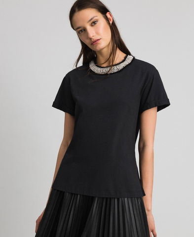 A photo of a women's t-shirt by an Italian designer that has been embellished with white pearls around its crew neckline.