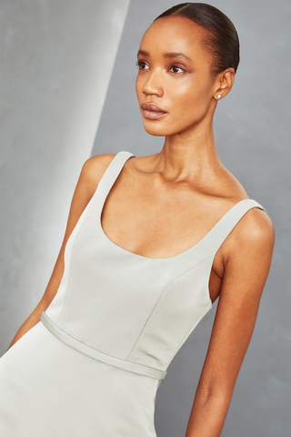 This is an images of a grey fitted women's sleeveless dress incorporating a scoop neck design element.