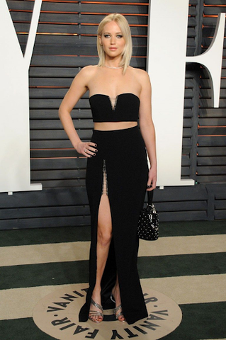 Jennifer Lawrence is wearing an outfit combined of sweetheart barrette and floor length black skirt with front leg slit.