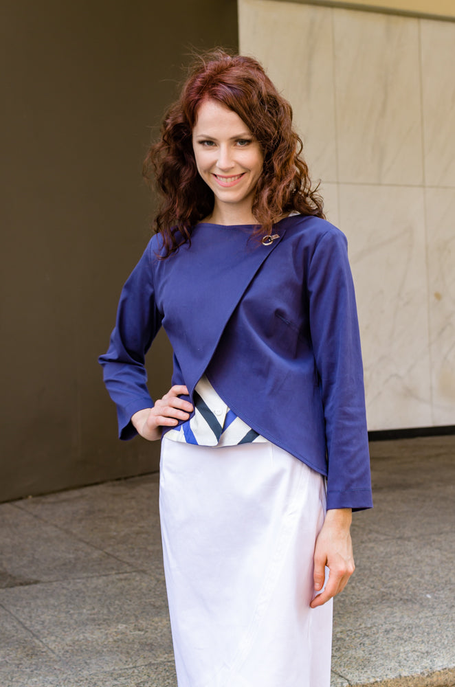 Our model, Jessie, is smiling because she feels great in our Overlapping Front Jacket in Navy Blue, Cap Sleeve Corset Top and Pencil Skirt with Scallop.