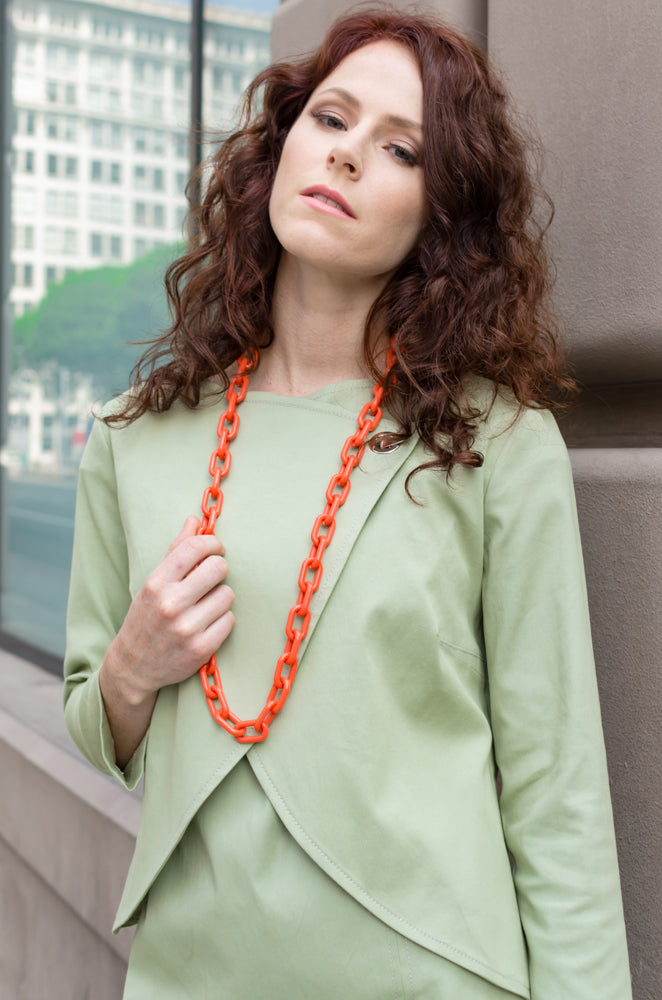 Our model, Jessie, is wearing our Overlapping Front Jacket in Sage Green with matching Drop Sleeve Scallop Hem Dress accenting the look with long chain necklace in orange.