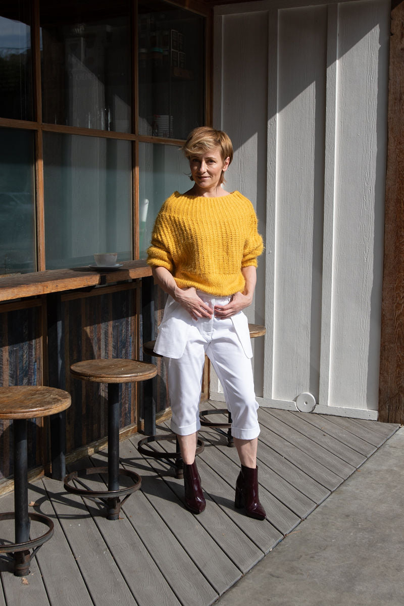 Our creative director, Inga Goodman, is wearing  a pair of Loose Pocket Cropped Pants in White from our latest Spring Summer collection combined with off shoulder yellow sweater and ankle boots in eggplant from her personal collection.