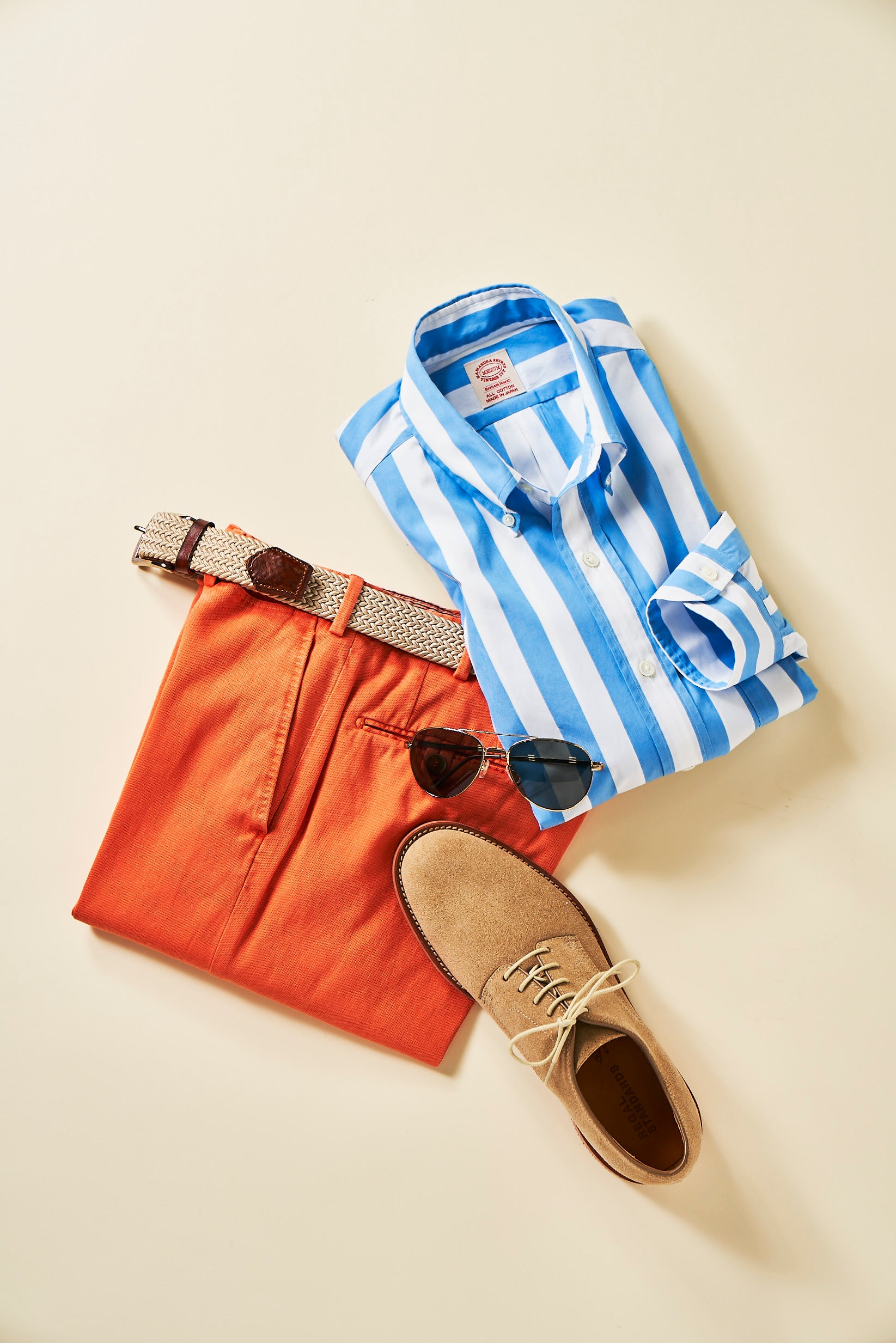A striped blue and white broadcloth shirt folded with orange trousers, shoes, and sunglasses