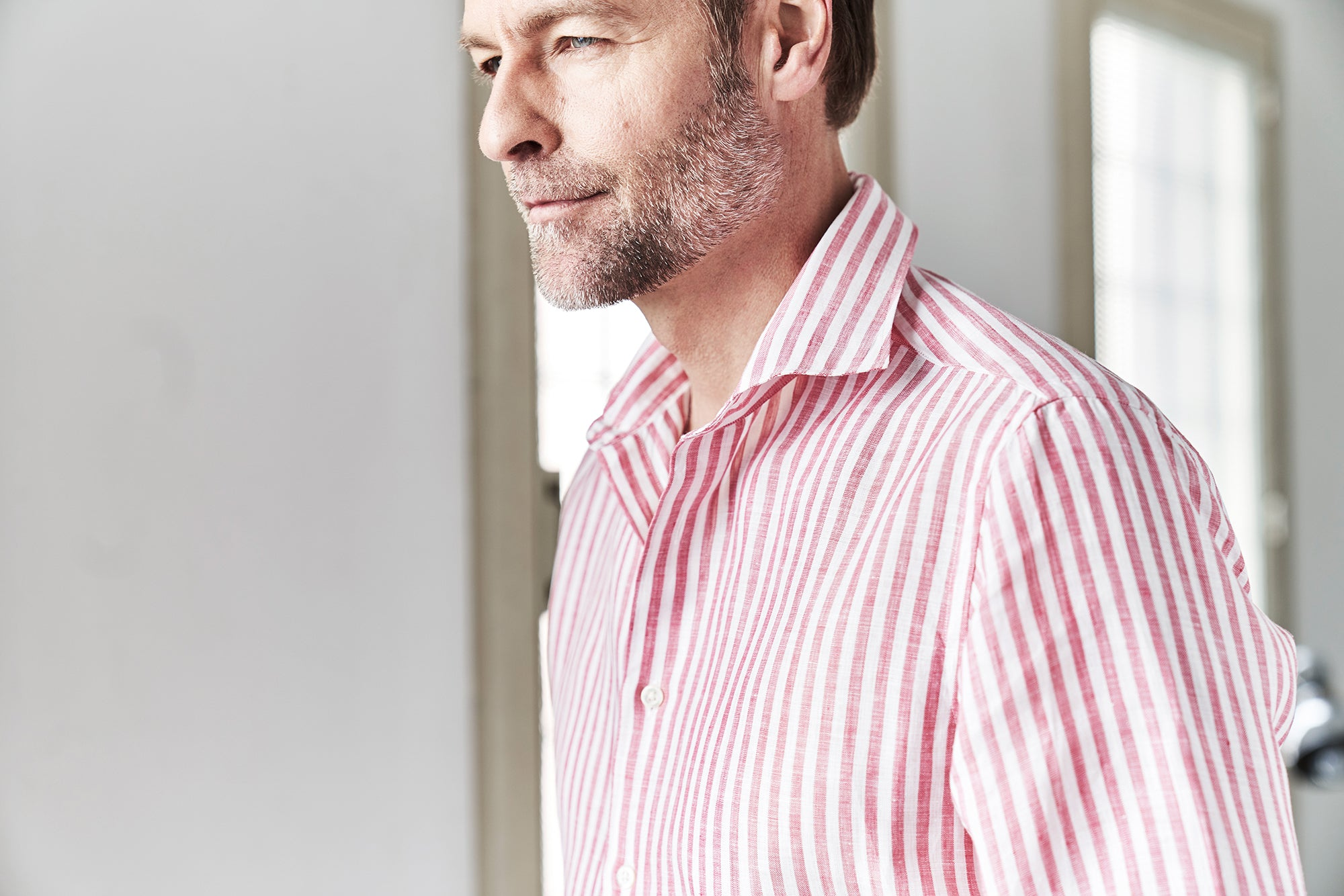 Profile of a man wearing a red and white linen shirt
