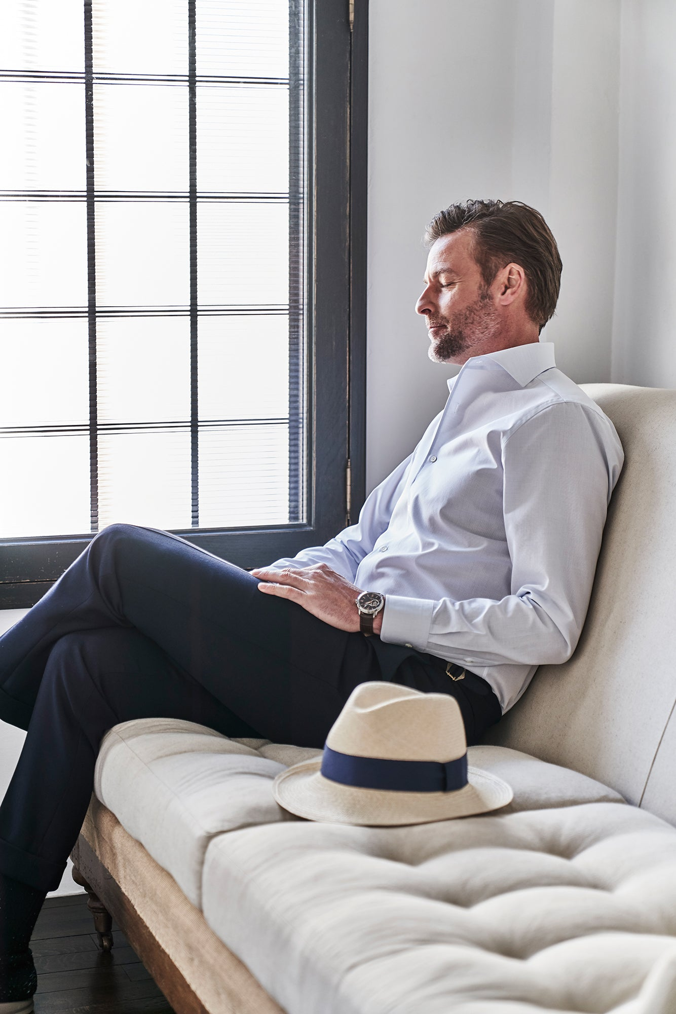 A man relaxing by a window on a couch in a dress shirt left unbuttoned at the top and trousers