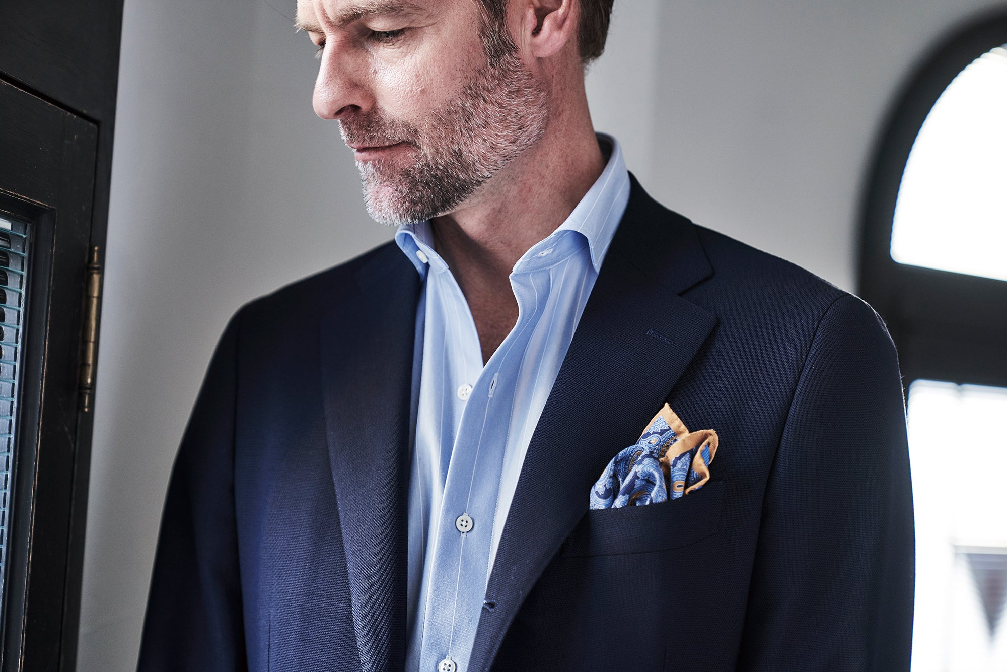 Man looking down in a jersey dress shirt and blazer