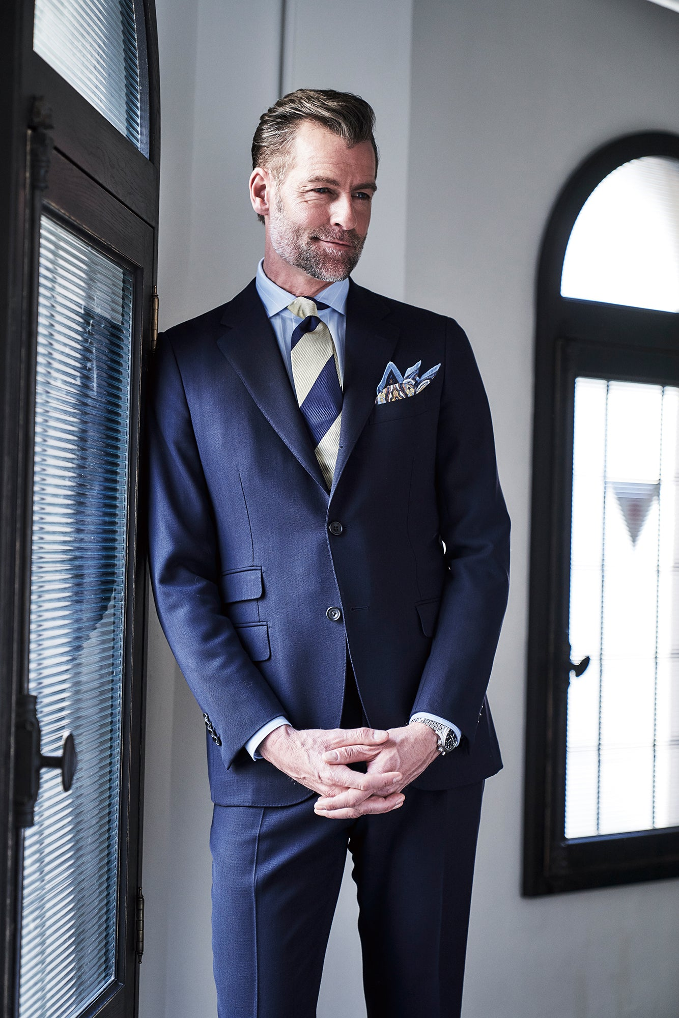 Man smiling in a jersey dress shirt, suit, and tie