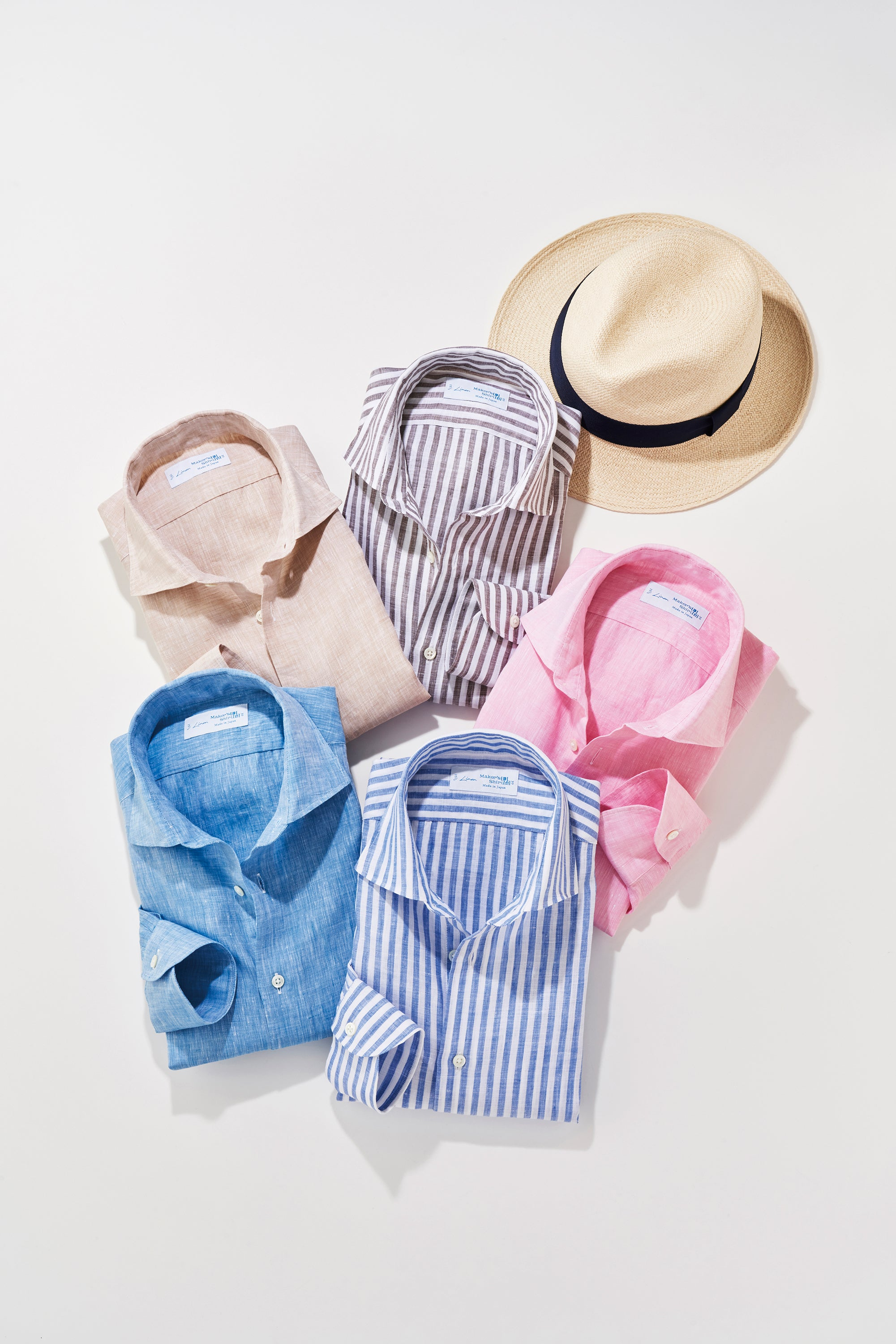 A pile of folded colorful linen shirts and a straw hat