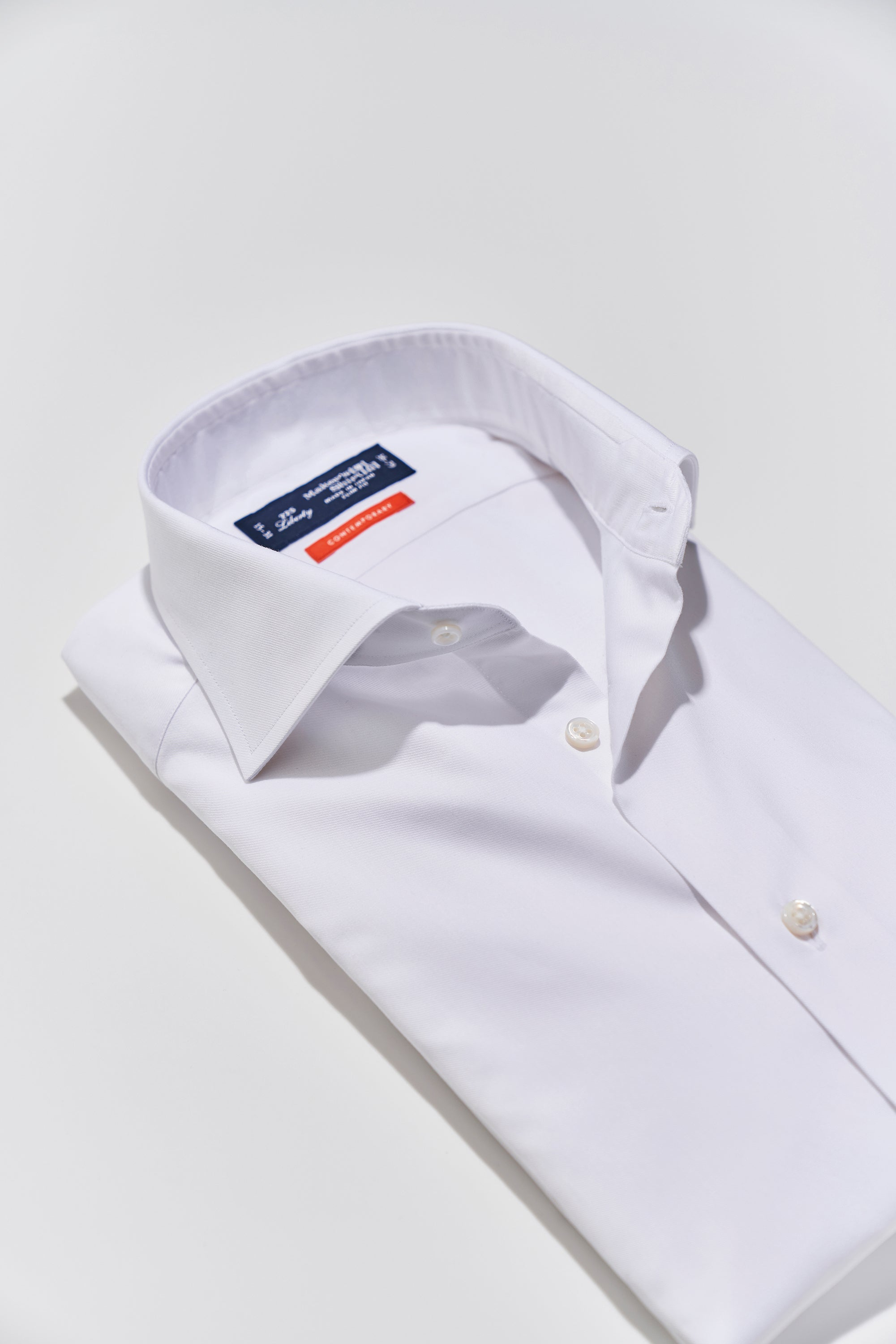 Folded white shirt with a uniquely wide spread collar