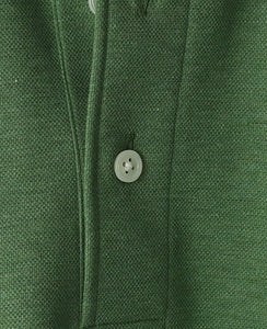 Close up of green cotton and polyester polo shirt