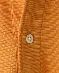 Close up of orange cotton and polyester polo shirt