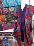 Tunic Dress using Dahlia flower fabric in colours Purple, Red, Green, Yellow with Purple Batik accent  showing other flower fabric next to dress