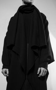 A huge, cosy and heavy draped coat with two zipper pockets inside and a raw-edge at the front and hem line. The coat is made in Berlin Germany.    Colour: black Material: overgarment   70% viscose, 30% PE                lining             100% PE