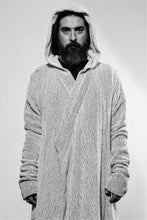 Front with hood up. A white draped cardigan in unregular grid optic with a crossing front. The cardigan is made in Berlin Germany    Colour: overgarment: white              lining: black, white Material: overgarment 100% cotton                lining               80% wool, 20% linen
