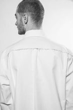 Detailshoot. A classic shirt with raw-edges at the yoke in the back and the left side at the front, the inner layer are white at the cuffs, yoke and stand. The shirt is made in Berlin Germany.        Colour: white, black Material: 90% cotton, 10% linen