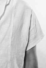 Detail. A simple, white and draped t-shirt  with shortsleeves and a raw-edge in the front, back and on the shoulderseam. The shirt is made in Berlin Germany.       Colour: white Material: 100% linen