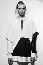 Front hood up. A stylish and cosy draped hoodie divided irregularly into black and white with big pocket in the front as well as a raw-edge seam in the center back. The sweater is made in Berlin Germany.      Colour: white Material: 95% cotton, 5% spandex