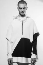 A stylish and cosy draped hoodie divided irregularly into black and white with big pocket in the front as well as a raw-edge seam in the center back. The sweater is made in Berlin Germany.      Colour: white Material: 95% cotton, 5% spandex