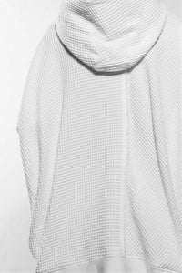 Detail back.A stylish and cosy draped hoodie divided irregularly into black and white with big pocket in the front as well as a raw-edge seam in the center back. The sweater is made in Berlin Germany.      Colour: white Material: 95% cotton, 5% spandex