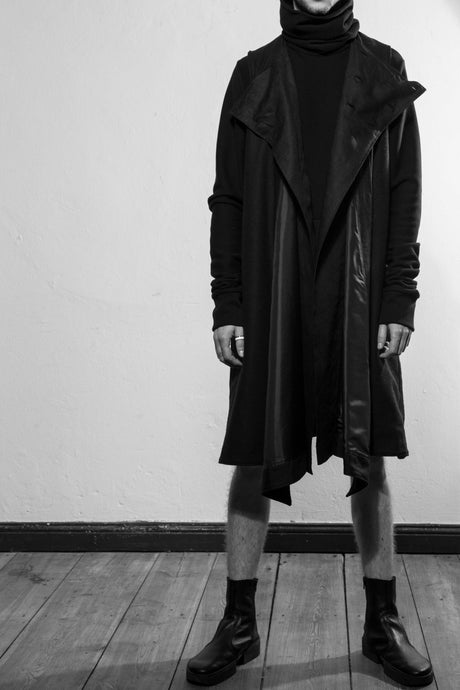 An avantgarde and chic black double layered draped vest coat with two pockets at the side seam of the inner layer. There is a high closing at the inner layer with six buttons. The coat is made in Berlin Germany.