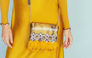 Embossed yellow & black leather belt bag with feathers