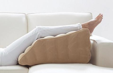legs resting on contoured pillow