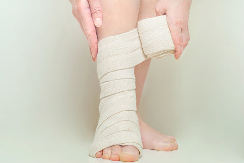 woman applying elastic compression bandage