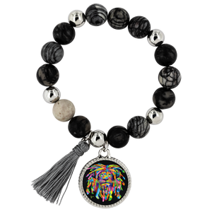 This Lyric style bracelet is a blend of natural onyx and dragon vein stone beads, paired with polished, silver-plated brass beads. Silver-plated charm with cord tassel. Assembled on a stretch cord for easy wear. One size fits all. Each bracelet comes in a re-usable black velvet pouch, perfect for storage or gifting.