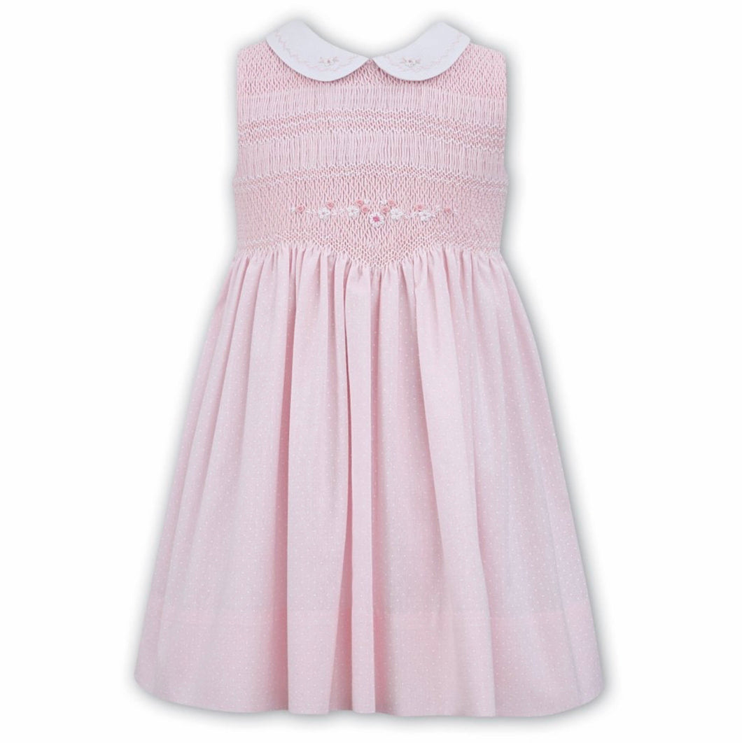 Beautiful Hand Smocking to Waist with Delicate Embroidered Detail to Bodice and Contrasting Peter Pan. Sleeveless Dress Finished in a Delicate Spot Print Fabric