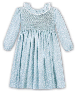 Girls Traditional Hand Smocked Long Sleeved Dress in Pretty Floral Print. Embroidered Detail with Lace Trim Frilled Collar