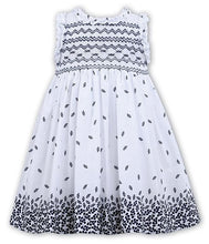 Hand Smocked Sleeveless Dress with Frilly Trim Around the Neckline and Sleeves. Finished in a Delicate Print Cotton