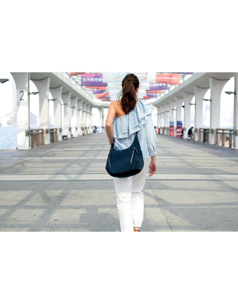 Women carrying pacsafe stylesafe anti-theft convertible navy colour crossbody bag back view