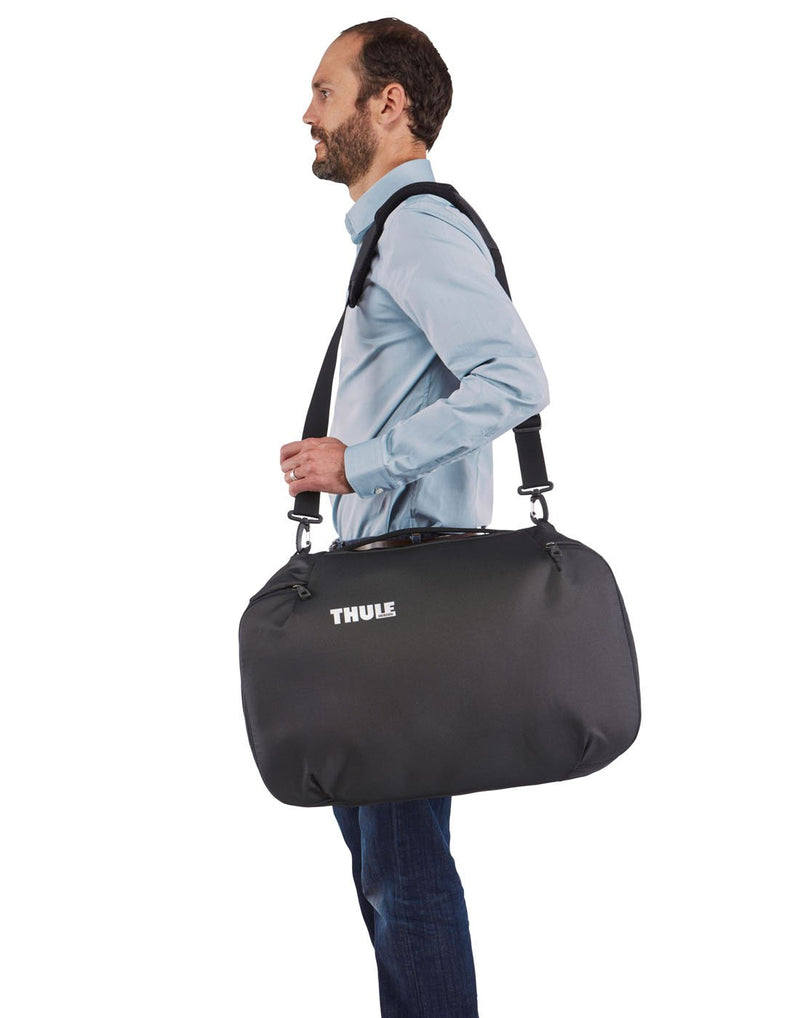 Men using thule subterra carry-on 40L dark shadow colour bag using as shoulder bag side view