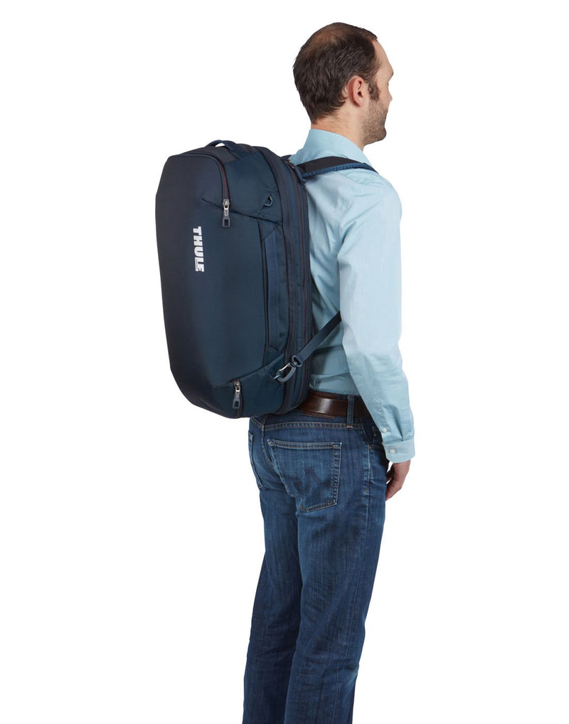 Man wearing Thule subterra carry-on 40L mineral colourbag using as backpack