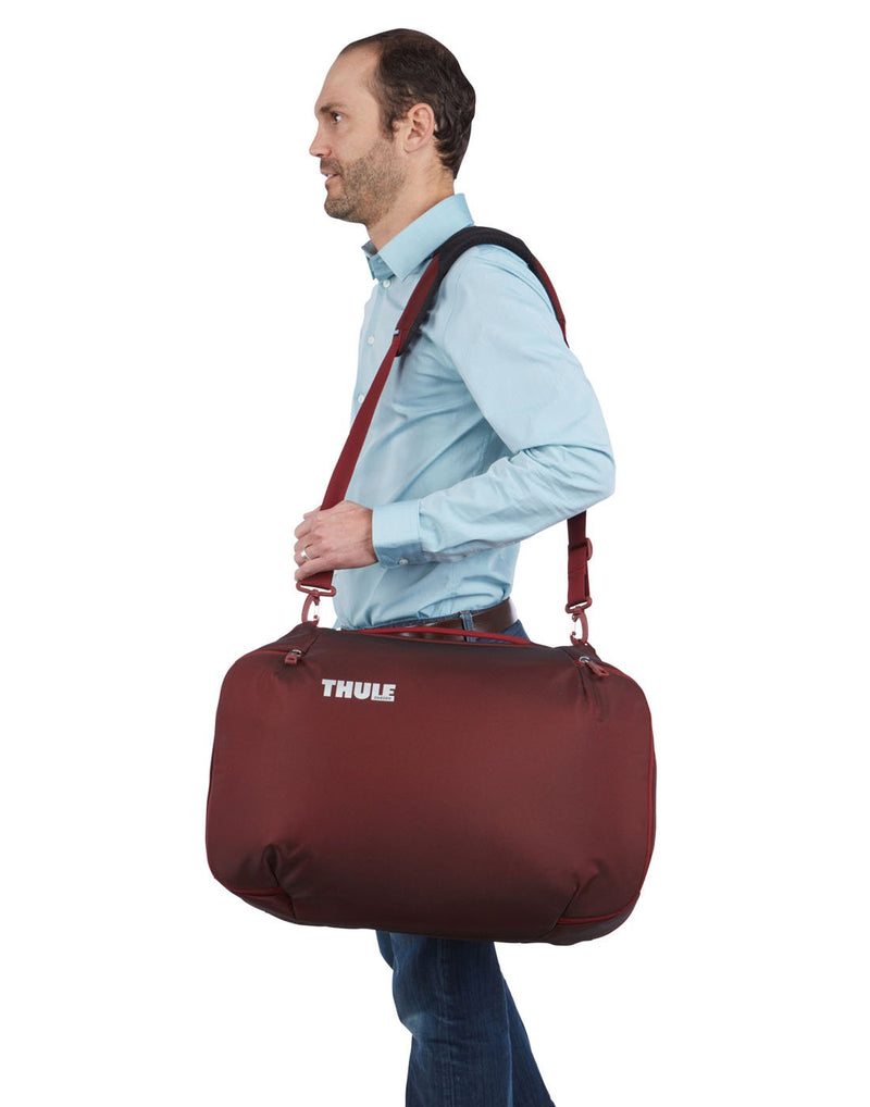 Man with Thule subterra carry-on 40L ember colour bag using as shoulder bag