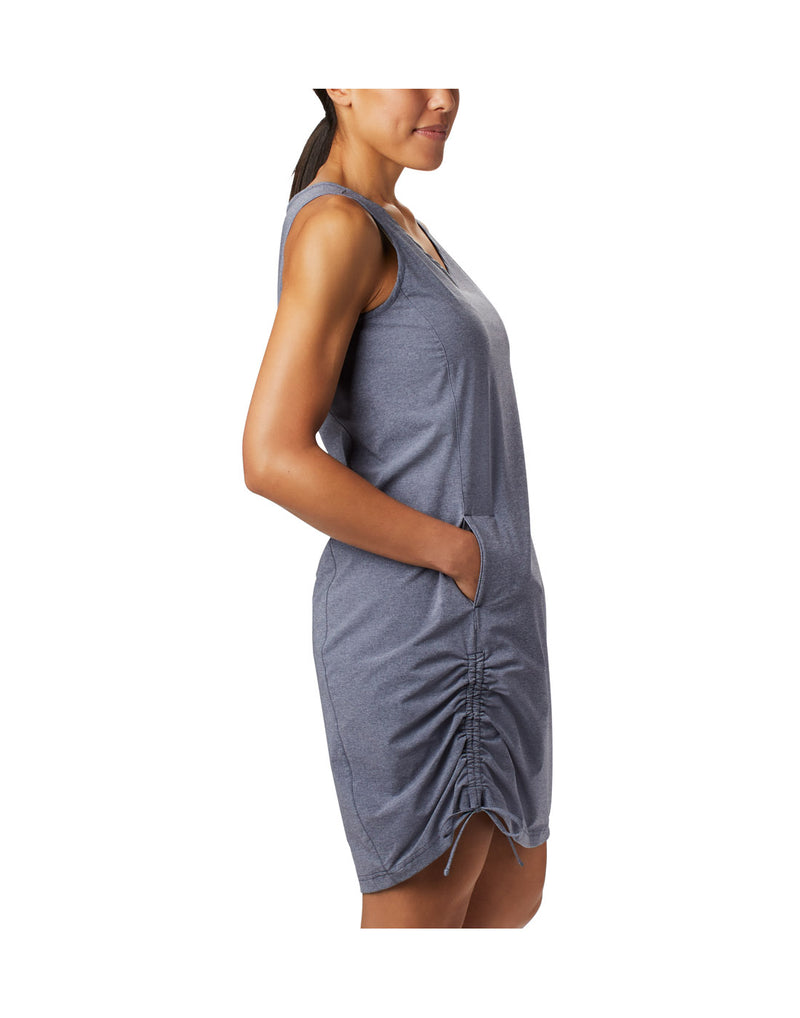 Woman wearing Columbia Women's Anytime Casual™ III Dress - nocturnal heather, side view with hand in right pocket and side strings tied
