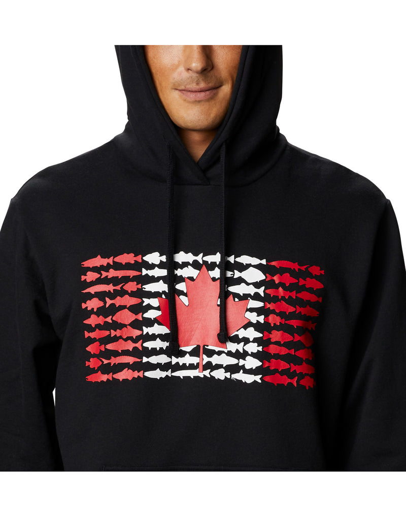 Model wearing Columbia Men's PFG Fish Flag™ Hoodie - black, close up of front showing Canada flag made up of small fish silhouettes