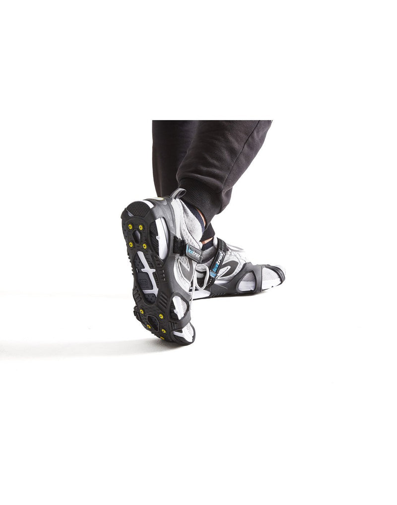 Icetrax V3 tungsten ice cleats with velcro straps on white shoes corner view