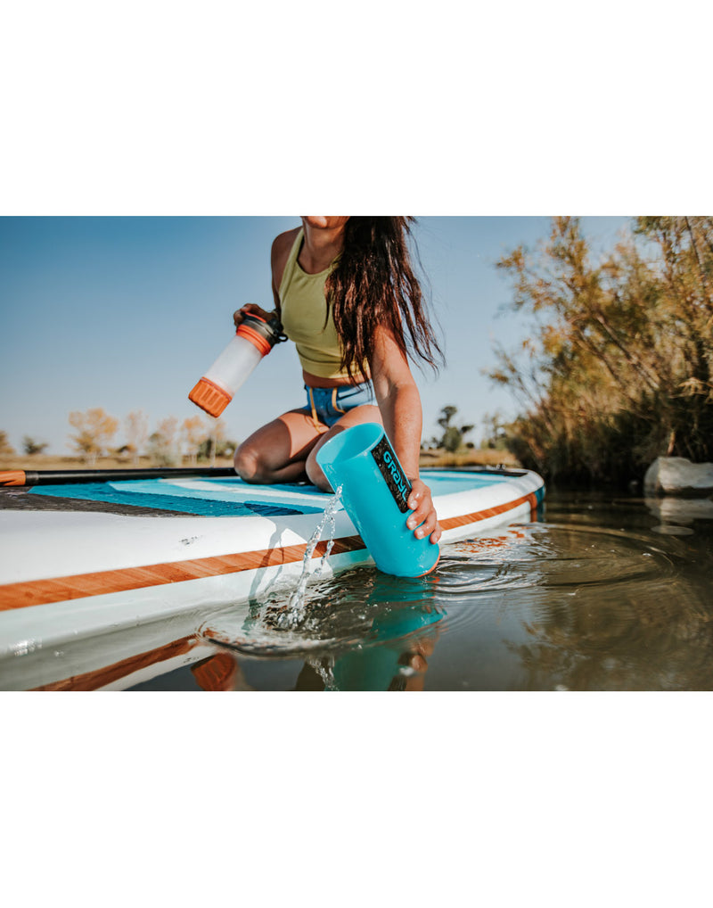 Woman scooping water into Grayl Geopress™ Water Purifier from side of a paddle board