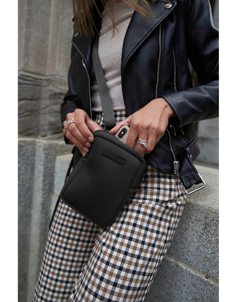 Woman wearing leather jacket and checkered pants taking a phone out of the MyTagAlongs mini crossbody that she has across her front
