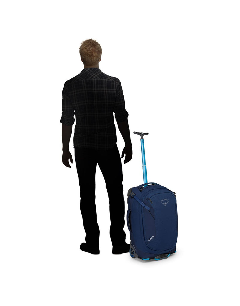 "Man standing beside osprey ozone 42L/21.5"" buoyant blue colour luggage bag front view"