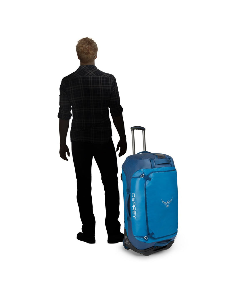 Men standing beside osprey transporter wheeled 90 kingfisher blue colour duffel bag body view