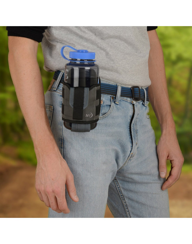 Man using Nite ize traveler™ drink holster with bottle attached to belt