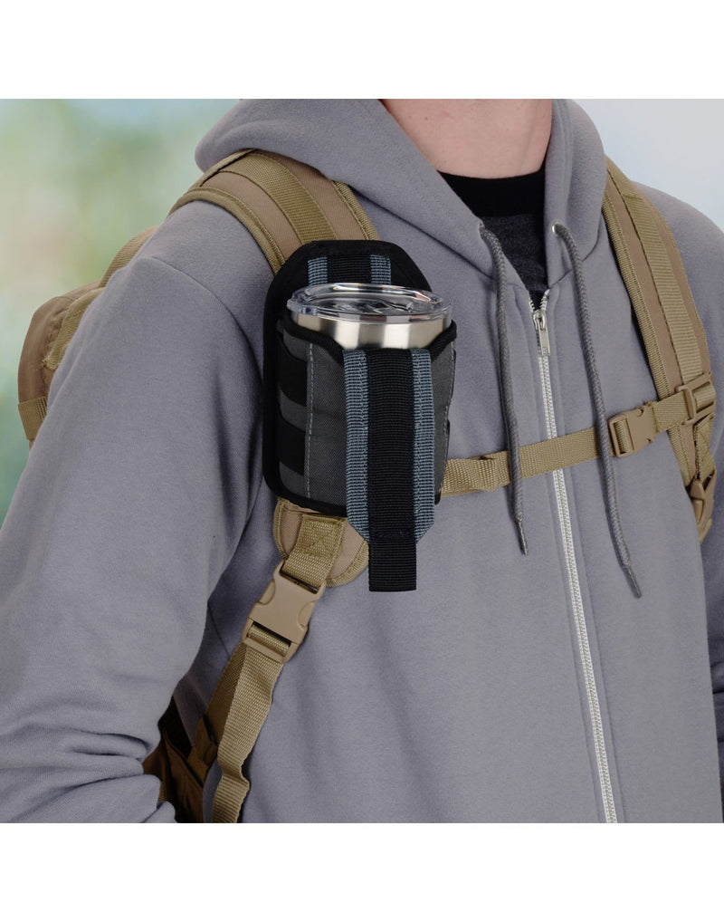 Man using Nite ize traveler™ drink holster attached to bag